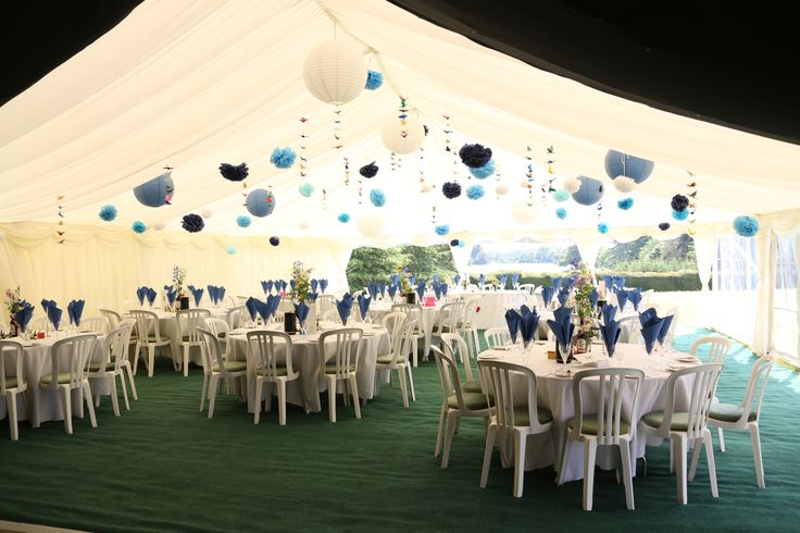 A stunning wedding marquee at Stansted Park, Emsworth, with hanging paper cranes, blue pom poms and paper lanterns...