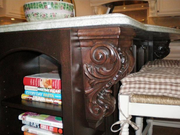 Decorative corbels on the end of the island with cookbook storage.