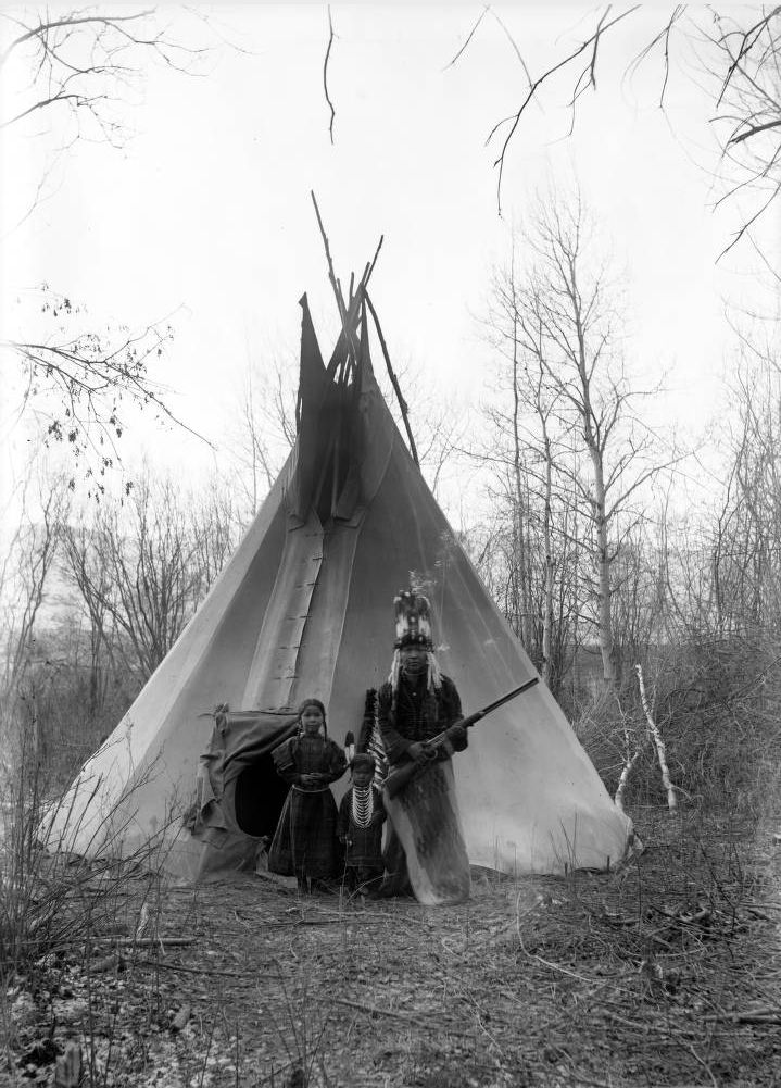 Filipe, a Native American man on the Flathead Indian Reservation in western Montana, stands in front of a teepee with two small children, Marie and Juan Pierre, on the reservation - Boos - 1900s