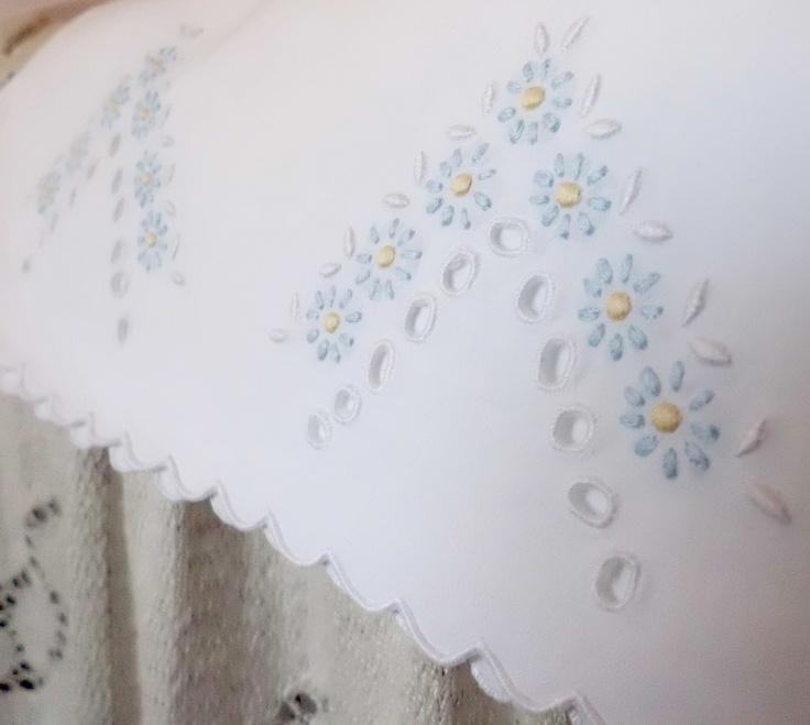 Detalle de un bordado en hilo de varios colores sobre tela blanca de una mudita de cama
