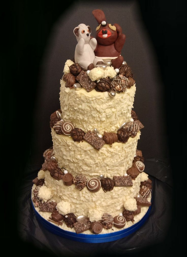 3 Tier White Chocolate Wedding Cake. Decorated with hande made chocolates and sugar models of his and hers childhood soft toys.