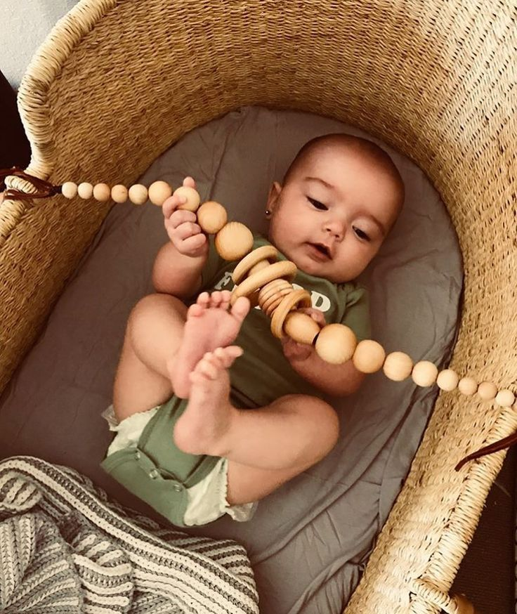 Baby playing with wooden beads in a vintage bassinet