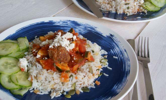 Door komijn en kaneel toe te voegen aan gehaktballetjes, creëer je een echt Grieks recept. De balletjes worden geserveerd in een tomatensaus met courgette en rijst.