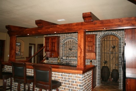 Prairie Heritage Design. In this wine cellar area, materials that were combined included bricks, knotty alder beams (new but distressed to look older), cherry and granite countertops, iron doors and iron niche doors.
