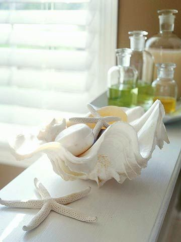 Shell Bowl    This is a pretty way to display large shells in a bathroom. One bowl-shaped shell is filled with a variety of shells and soaps, then topped with a pretty starfish.