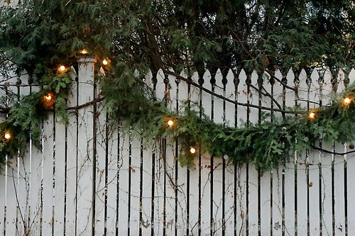 and old white fence and Christmas garland with lights - gorgeous.