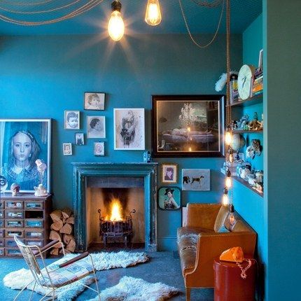 Kooky boho living space. Stunning aqua walls, lush fur rugs, homely open fire place, distressed leather couch and eclectic collectibles.