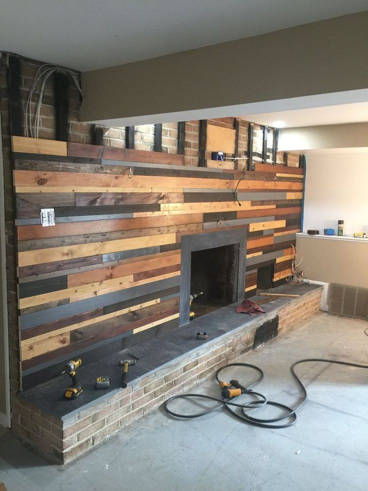 A man nails blonde boards to the wall, and a few steps later...THIS fireplace idea is amazing!