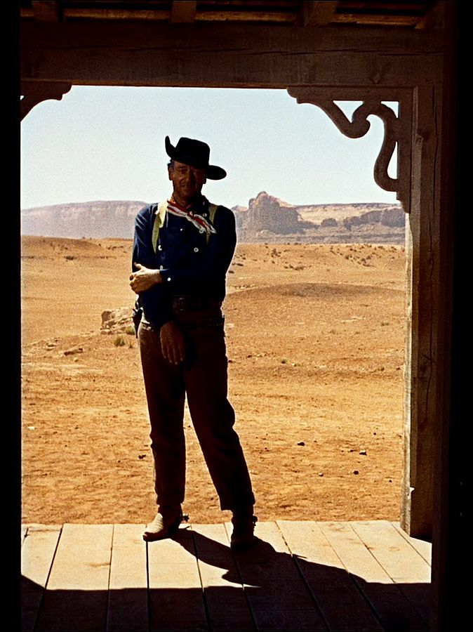 John Wayne in Ford's 'The Searchers'. In the final shot, Wayne pays tribute to Harry Carey...