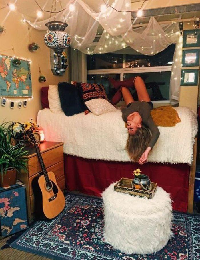 chambre d'étudiant, style d'aménagement boho chic, decoration interieur appartement, voilage blanc transparent suspendu au plafond, pouf rond en peluche blanc, tapis carré en bleu, blanc et fuchsia, meuble en couleur bois, guitare appuyée au meuble, jeune fille étendue sur le lit en pose relax
