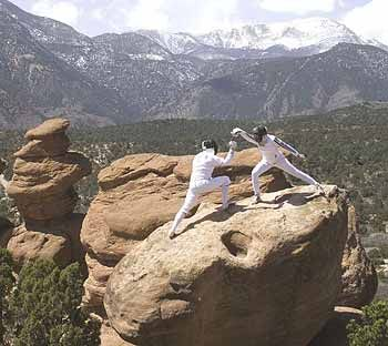 Pentathlon Olympic gold medalist Maciej Czyzowicz and U.S. modern pentathlon coach Elaine Cheris demonstrate a fencing stance atop boulders at the Garden of the Gods Park near Colorado Springs. Fencing is one of several nontraditional activities recommended for teenagers who want to earn Venturing's sports and fitness medal, the Quest Award.
