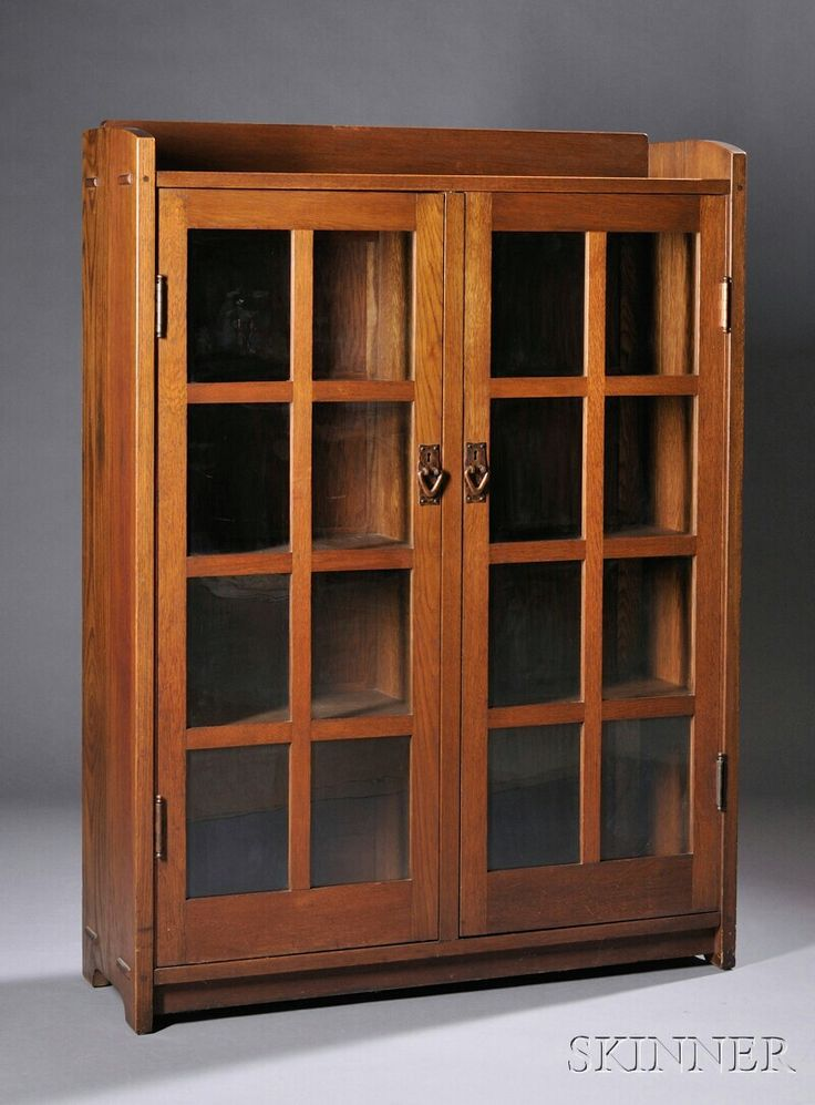 Gustav Stickley Two door Bookcase, oak wood, New York, 1912-1916.  Gallery top over two doors with eight paines and copper pulls, case with through tendons fitted with three shelves, 56.25 H. x 41.75 w. x 13 D.