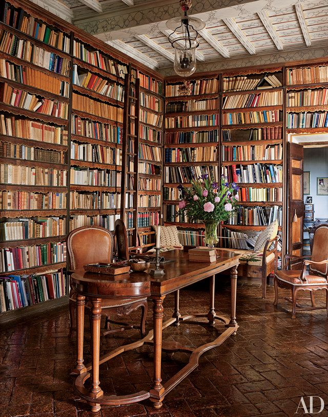 In the library of Count Raniero Gnoli's apartment near Rome, scalloped strips of hand-decorated leather protect books from dust. He designed the glass-and-iron bell-jar lantern and had it handmade in India; a late-18th-century Italian armchair is pulled up to the 19th-century walnut table.