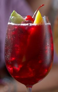 Red Sangria...Ingredients: Merlot - 4 oz, Grand Marnier - 1 oz, Pomegranate Juice - 1-2 oz, Mango Juice - 1-2 oz, Oceanspray Cranberry Juice - 1 oz,    Soda Water - 2 oz   Procedure: Put ice in wine glass until glass is full. Add all ingredients. Transfer into shaker tin and mix back and forth 2 or 3 times to thoroughly mix. Add soda water. Add cherry, mango, lime wheel as garnish.