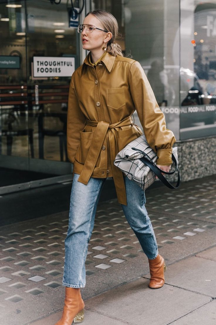 spring style - cropped jeans, brown booties, beige cropped trench coat, low bun, statement glasses - street style