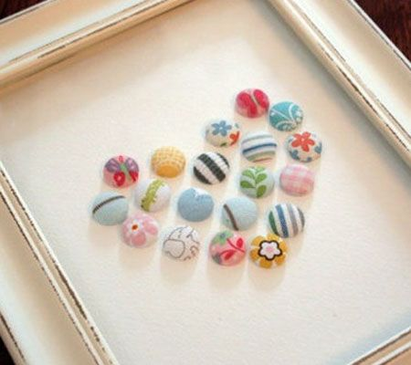 "Baby Heart Shadow Box - made from old baby clothes wrapped onto buttons.  I think I'll try this for her first birthday, but make an ""E"" instead of a heart (even though the heart IS super sweet)...that way, each (future) baby gets one with their own initial on their 1st birthday."