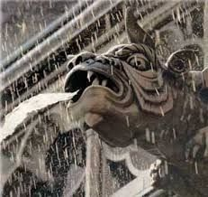 This is an example of a gargoyle doing their practical purpose.  The mouth of the dragon is used to drain the water during the rain.