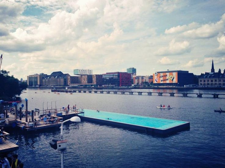 Berlin's Arena Badeschiff pool floats inside of the River Spree, where visitors can swim in clean water and enjoy views of the surrounding city. Food, drinks, music, and lounge chairs are also available from open to close.