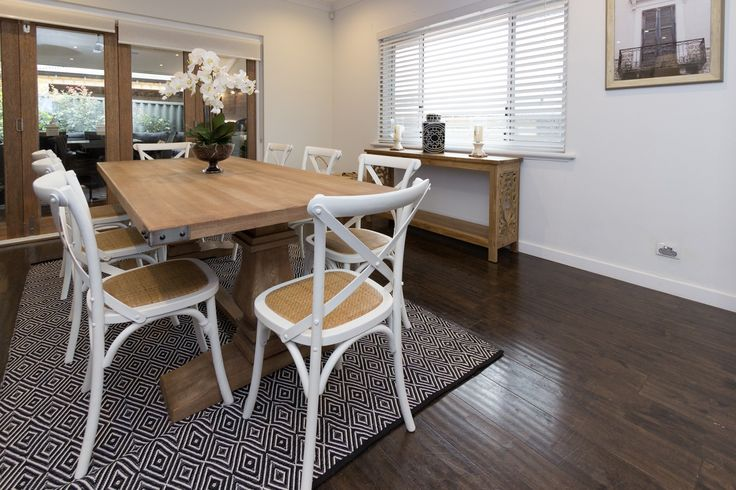 A casual dining room with a large timber table, white cross back chairs and a…