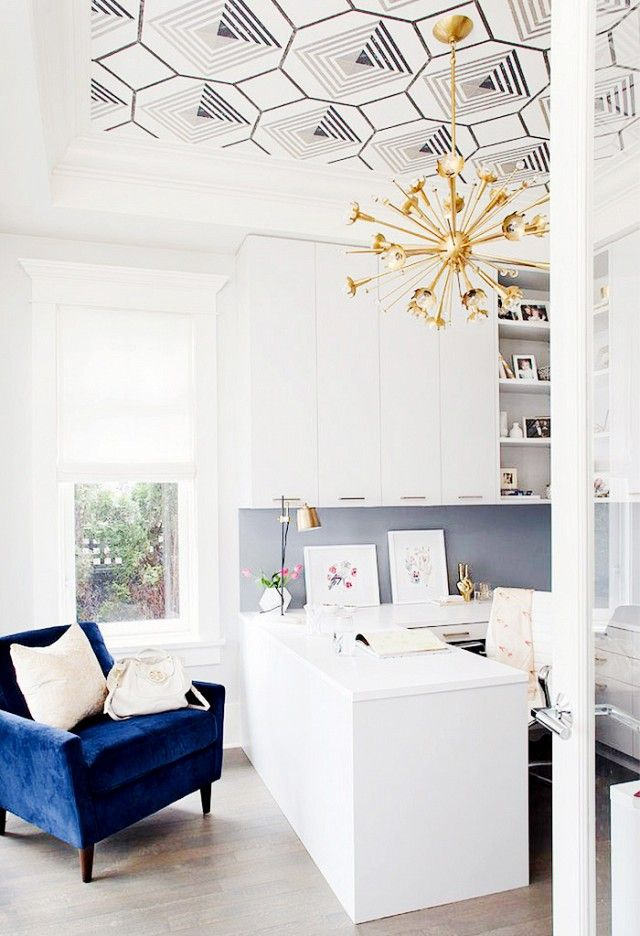 This clean and simple office gets a dose of modern cool with a graphic wallpapered ceiling and a sputnik chandelier. The navy triangles play well with the blue chair, and the gray provides a nice...