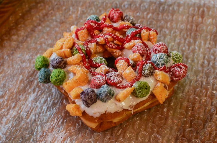 """""""Cereal Killer."""" A square, yeast-raised doughnut -- topped with vanilla glaze, mini marshmallows, piped red frosting, Crunch Berries and Cap'n Crunch cereal."""