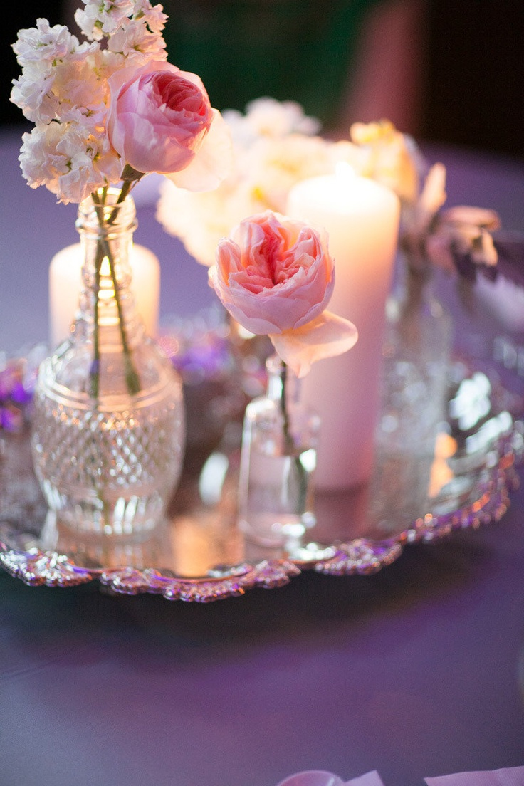 Vintage vases holding small arrangements with candles amongst the flare... gentle and feminine
