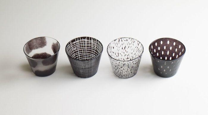 彼女のガラスの器を代表するガラスの器は、「めんちょこ」。 左から、「モウモウ」「センセン」「ホリホリ」「ツブツブ」。ネーミングそのままのガラス表現。 新しいスタンダードに相応しいフォルムは、猪口としてだけでなく、グラスやデザートの器としても使えます。