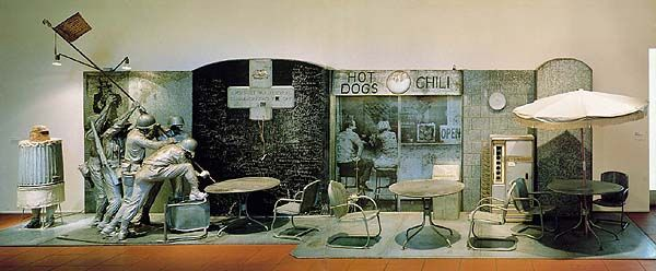 """Ed Kienholz - Portable War Memorial, 1968. Museum Ludwig, Cologne. This piece suggests that war has become a part of everyday life to which we have become oblivious. The tableau is divided in two part: left, images of the military and of patriotic war memorializing; right, customers at a snack bar. That the """"memorial"""" is """"portable"""" suggests that the wars are endless and interchangeable, and not all that signficant. The chalkboard allows victims' names to be erased and replaced. (Delahoyde)"""