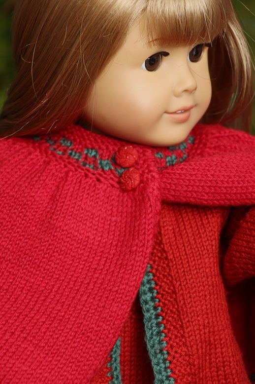 I have designed a ovely red Cape with green borders.  I hope you will like to knit it for your doll! Målfrid Gausel