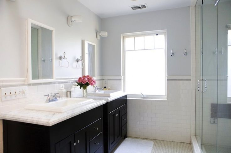 Erinn Valencich    Lovely bathroom with lilac blue walls paint color, subway tiles backsplash, espresso stained double bathroom vanity, marble counter tops, light gray walls, white recessed medicine cabinets mirrors and frameless glass shower.