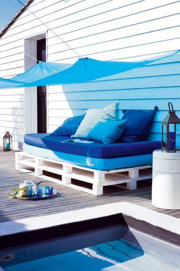 Un lit d'extérieur fabriquée avec deux palettes peintes en blanc et deux matelas bleus superposés ou côte à côte