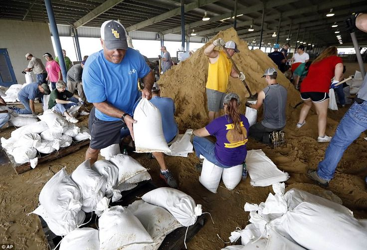 A volunteer loads sand bags on a pallet as others fill them for resident distribution in preparation for further rain, tornadoes and widespread floods in Louisiana on Wednesday