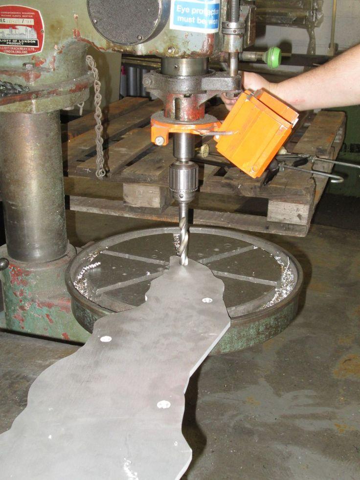 Drilling holes into the aluminium using a pedestal drill.