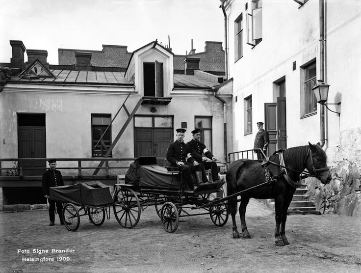 Helsingin vanhan paloaseman pihalla, Konstantininkadulla, esitellään ensimmäisiä sairaankuljetusvaunuja. Foto: Signe Brander, 1909.