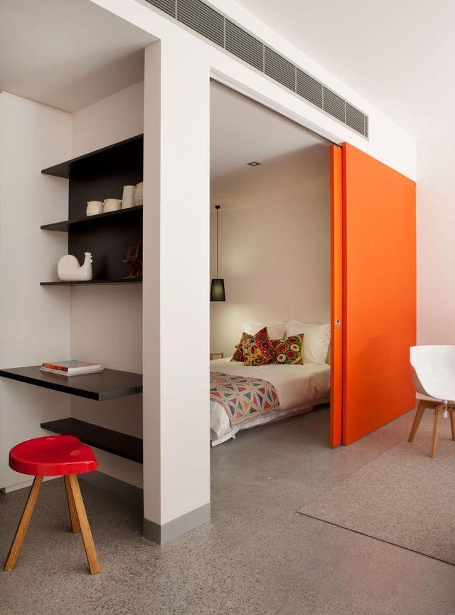 Un coin chambre savamment dissimulé derrière une paroi coulissante orange