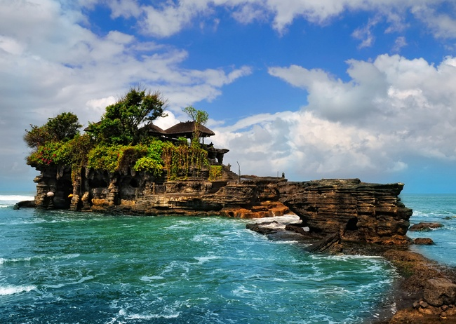 The Sunset Temple, Tanah Lot ~ Legend has it that 15th century priest Niratha came to rest at the rock formation along one of his journeys because of its beauty. He told the fishermen who brought him food and gifts to build a shrine because he felt it was a holy place to worship the Balinese sea gods.