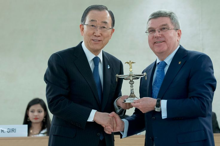 Thomas Bach (right), President of the International Olympic Committee (IOC), presents Secretary-General Ban Ki-moon, on behalf of the UN, with the Olympic Cup Award during in the Olympic Flame Ceremony at the Palais des Nations in Geneva. UN Photo/Jean-Marc Ferré