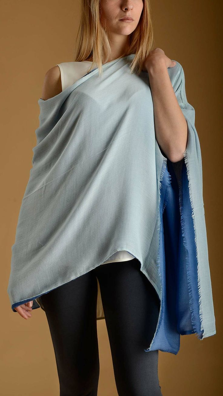 Double face modal ponchos in blue and light blue characterized by a wide boat neck, asymmetric bottom, raw cut detail, 90% modal 10% cashmere.