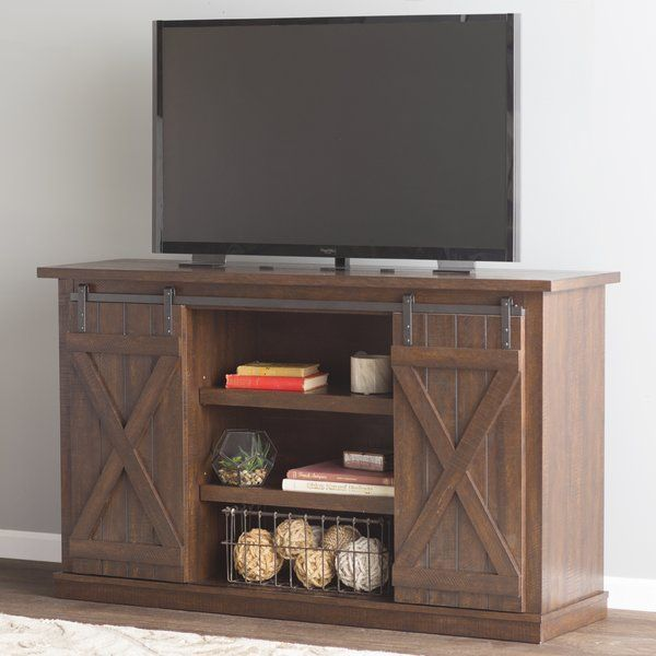 Inspired by the designs of rustic barns and mountain lodges, this charming TV stand will bring quaint charm and essential storage space to your home. The clean-lined design and neutral palette gives this piece a touch of traditional style and versatility, while the slatted wood design with cross beam accents, and the pewter metal hardware anchors it in rustic style. For optimal functionality, all shelves are adjustable and rear holes for easy cable management and ventilation. Top this…