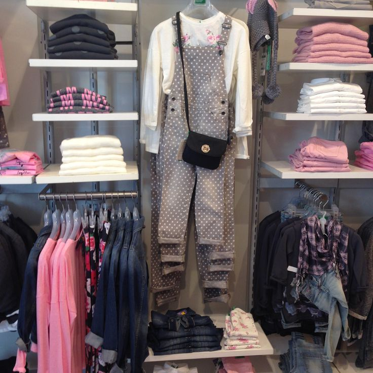 #spur fixtures #garment rails #fashion displays #clothes shop designs. Wall mounted silver uprights with white shelves and chrome clothing rails. Coat hangers to match. A low cost effective clothing display for retail clothing shops.