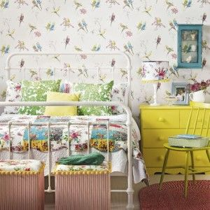 For a truly vintage theme, go for small patterns that are usually pretty, often floral and generally in primary colours. Here, budding flowers and budgies festoon the room,