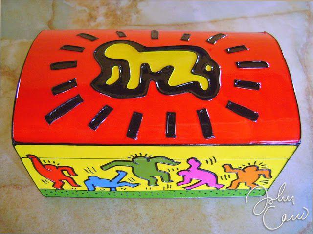 Baúles: Haring | JohnCano Este Baúl tiene como tema los dibujos del artista estadounidense Keith Haring, es su sencillez se encuentra lo bello y armonioso.  Cada lado del Baúl tiene una de sus creaciones pop. En la tapa esta el bebé radiante gateando, en los lado derecho esta la pareja de enamorados levantando el corazón, en el lado izquierdo esta el perro dj, y en el lado delantero y posterior están los hombres bailando.