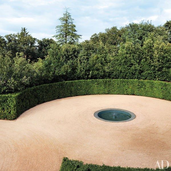 A fountain anchors one of the entrance courtyard's gravel circles, which…