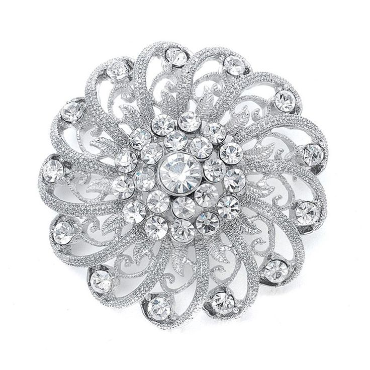 """Aspecial occasion pin that glimmers with swirling filigree spirals. This beautiful silver brooch is accented with sparkling clear crystals and measures 2 1/4"""" w. Our crystal pin will make a great accent for any bridal or bridesmaid dress."""