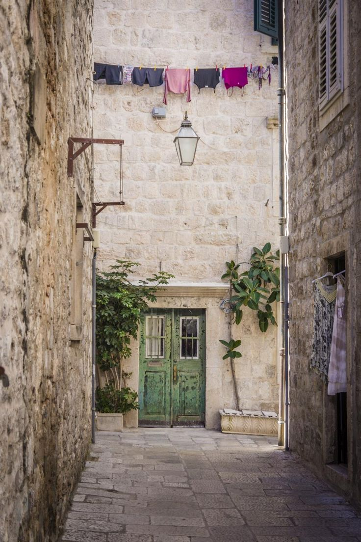 Alleyway with old green door and line of colourful washing, Dubrovnik.