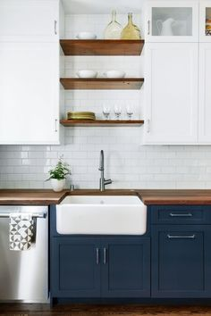 Dark base cabinets, white upper cabinets. Open wood shelves and big farmhouse apron sink