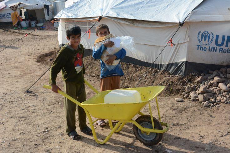 Syrische jongentjes op pad met een kruiwagen in Gawilan, een vluchtelingenkamp in Irak.: