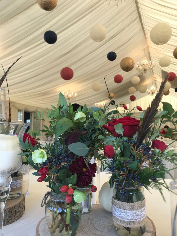 Jam Jar Arrangement: Red roses, Red Spray Roses, Rosehip, Viburnum Berries, Calla Lilies, Dahlias, Helleborus, Blue Thistle, Asparagus Fern, Pheasant Feather on a log base with a Gourd