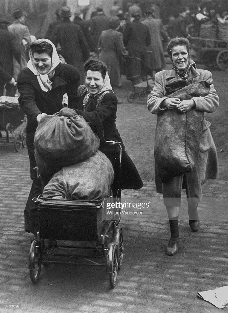 Having queued in the cold for fuel at the Gas Light and Coke Company depot at Nine Elms, three women are happy to cart away their precious coke.  February 15, 1947