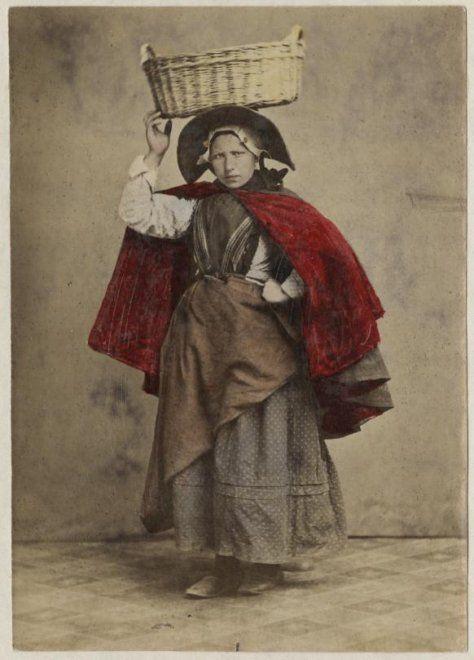 Vrouw in Scheveningse dracht; negotiante (visverkoopster) met vishoed en vismand; zij draagt een katoenen gebloemd jak, een donkergekleurde katoenen rok, omgeslagen schort, een heel smal doekje, een schoudermantel waarschijnlijk met rode baai gevoerd, muts met klappen, ijzer met stukken, haar in een toer. ca 1890 #ZuidHolland #Scheveningen